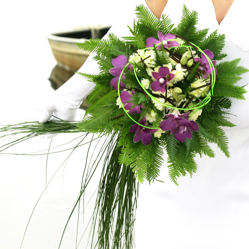 Umbrella fern and steel grass are used to create a wedding bouquet.