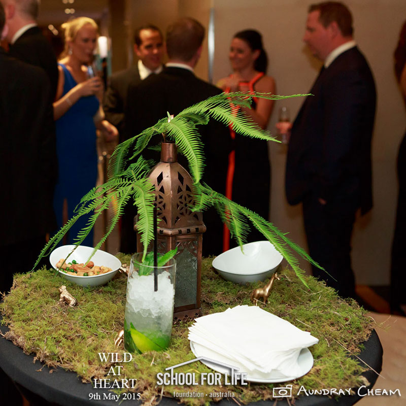 Umbrella fern is used in a table setting to compliment a Midori cocktail.