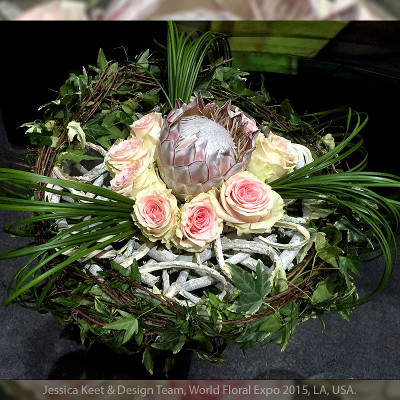 Steel grass is curved around an ivy wreath and apricot roses.