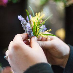 Florist assembles buttonhole featuring Australian wattle