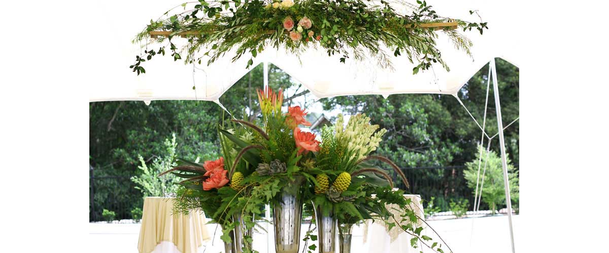 Top Table arrangement and chandelier of tropical flowers and native foliages