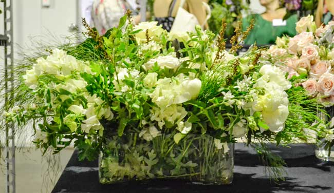 A low glass vase of white cottage flowers with Stenocarpus, Emu Feather and Bronze Rush/Dingo Tails. Perrots
