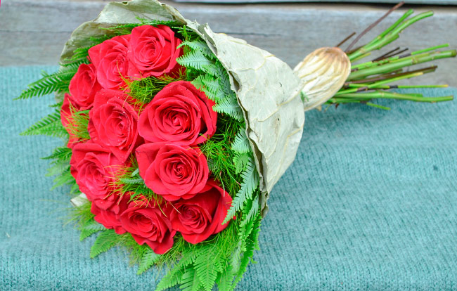 Lavish red rose bouquet with native Koala Fern & Umbrella Fern wrapped in a lotus leaf.